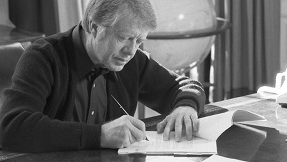 A black and white photo of Jimmy Carter signing the Presidential Memorandum.