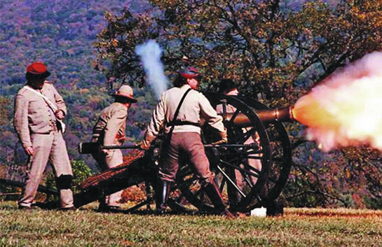 Actors as soldiers fire the cannon during a Civil War battle reenactment