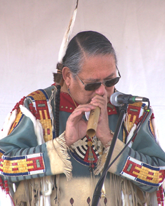 A man wearing Native American clothing plays a wooden flute into a microphone.