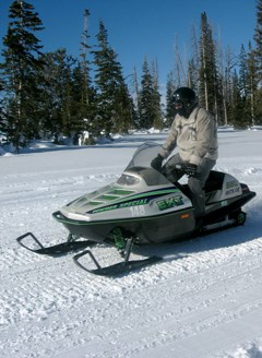 Person on a snowmobile in a winter landscape.