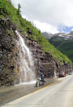 A motorcycle and two automobiles drive past a waterfall on a scenic mountain road.