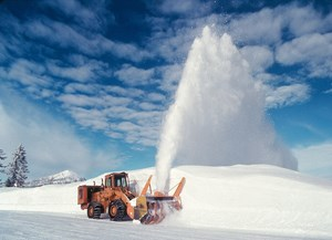A snowplow blows snow off of a road.