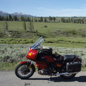 Red motorcycle parked on roadside with meadow, trees, and mountains in background.