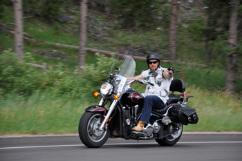 Man wearing helmet riding a motorcycle on a road through the woods.