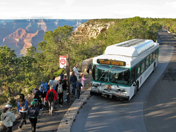 People boarding a shuttle bus on the rim of the Grand Canyon.