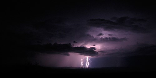 Lightning flashes turn the sky purple as they backlight black clouds in a dark night sky