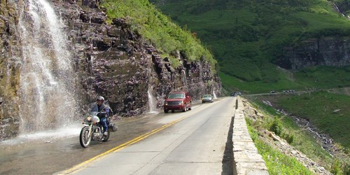 Motorcycle driving up a steep road, with several vehicles behind and a waterfall to the left