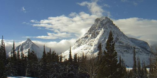 Two snowy mountain peaks, with an avalanche rushing down the side of the larger one. Evergreen trees in the foreground.