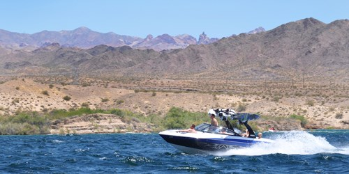 People ride in a motor boat on blue water with desert hills in the background