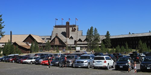 Cars in a parking lot in front of a large lodge building