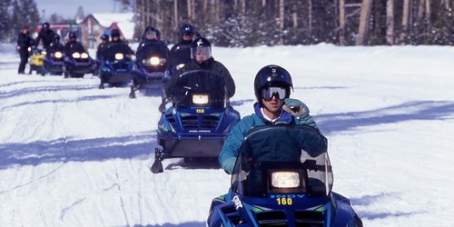A group of people with helmets driving snowmobiles across the snow