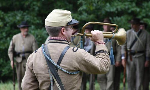Man in military uniform playing a bugle