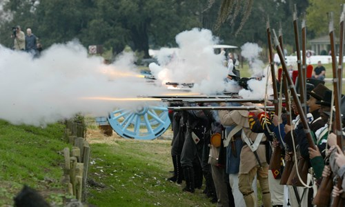 Re-enactors in soldier uniforms firing muskets