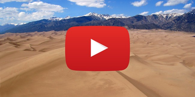 YouTube play logo over a field of sand dunes with mountains and blue sky in the background.