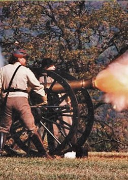 Costumed actors as Civil War soldiers fire the cannon during a battle reenactment
