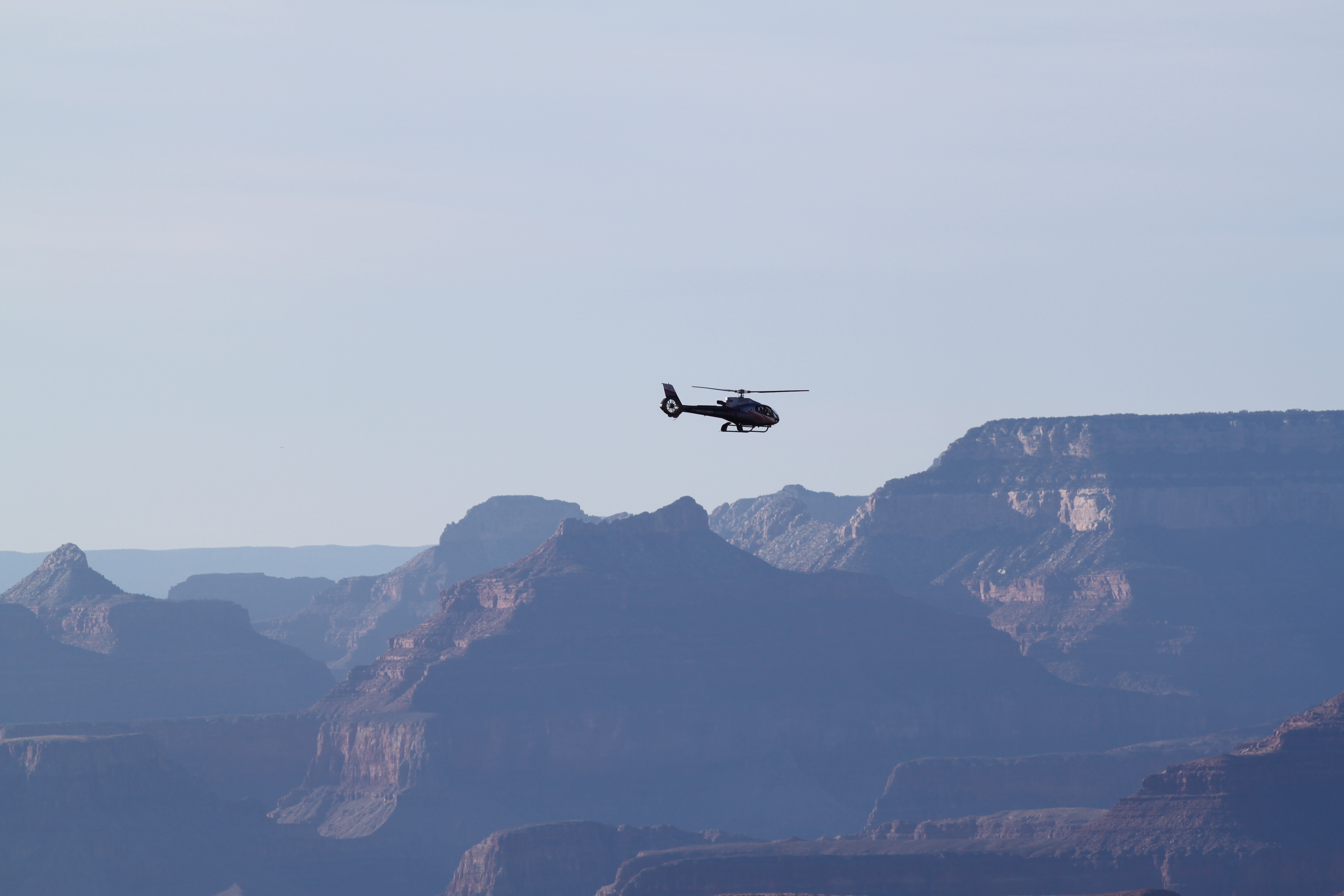 Tourists experience the wonder of Grand Canyon National Park from the vantage of a helicopter.