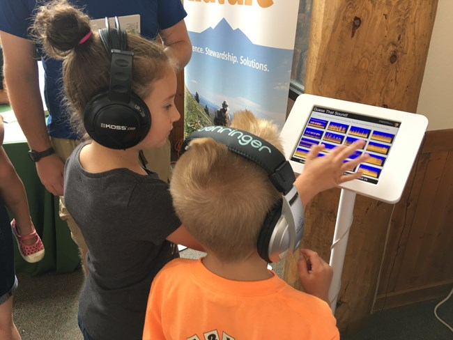 Rear view of two children interacting with a touch screen displaying spectrograms.