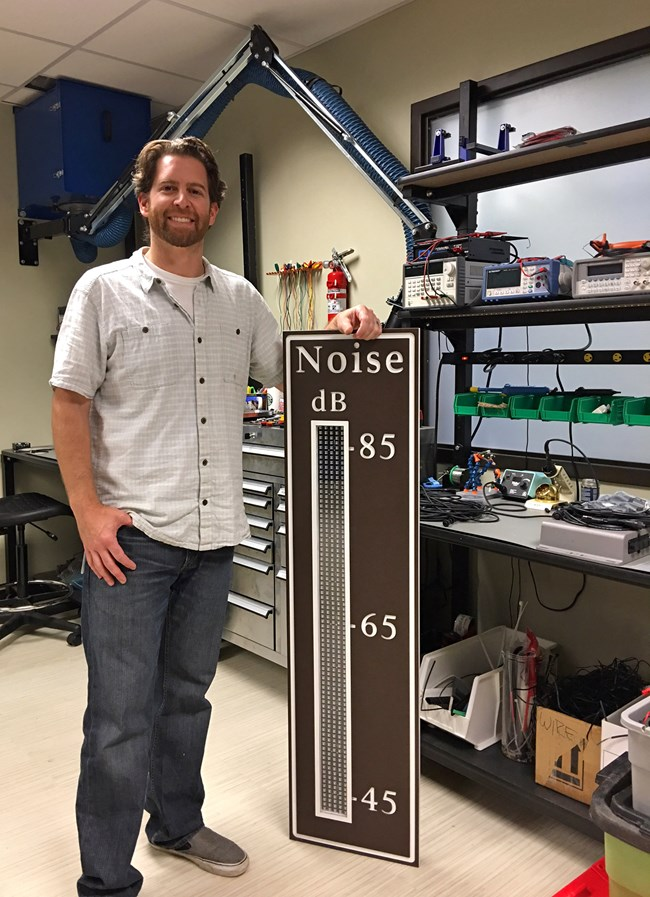 NPS acoustic technician Chris Garsha stands beside a newly created noise traffic display sign.