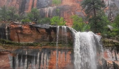 Frontal view of a waterfall over red rock framed by forest.