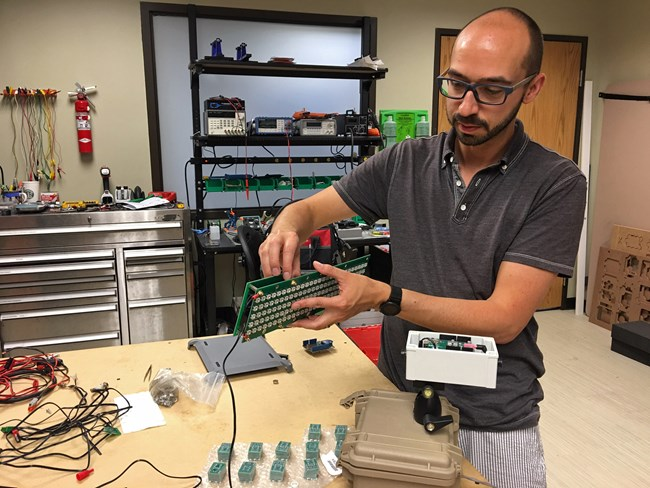 NPS acoustic technician Damon Joyce shows some of the electronic components that comprise the noise level display signs.