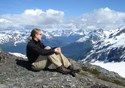 A female hiker sits atop a mountain and contemplates the quiet of her surroundings.