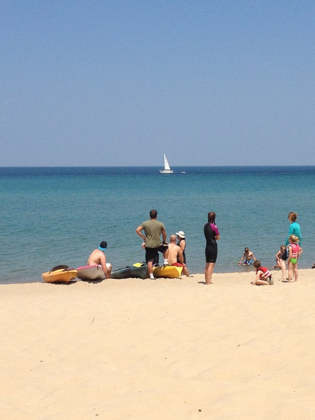 Kayakers and beach visitors watch a sailboat pass by offshore of Miners Beach.