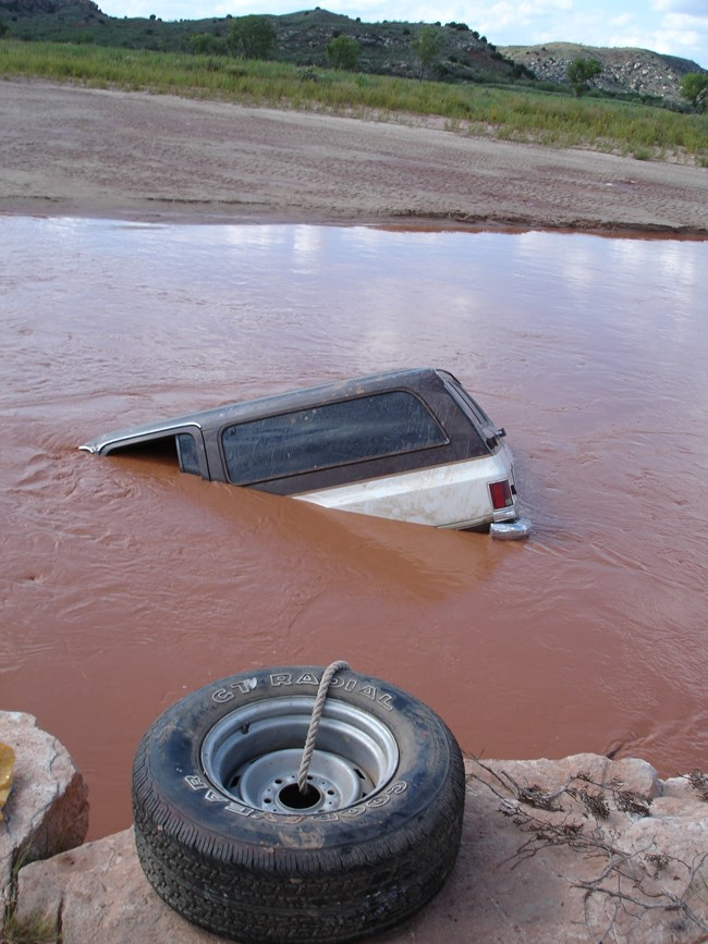 A vehicle is in a river and anchored with a tire.