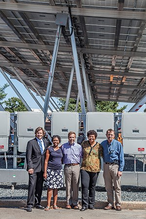 Four people pose under a large solar panel array.