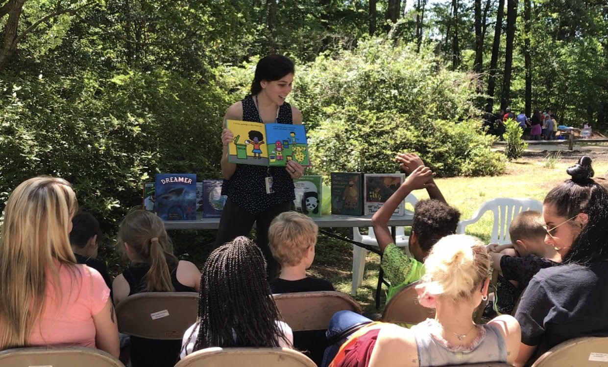 A Librarian presenting a book to the classroom