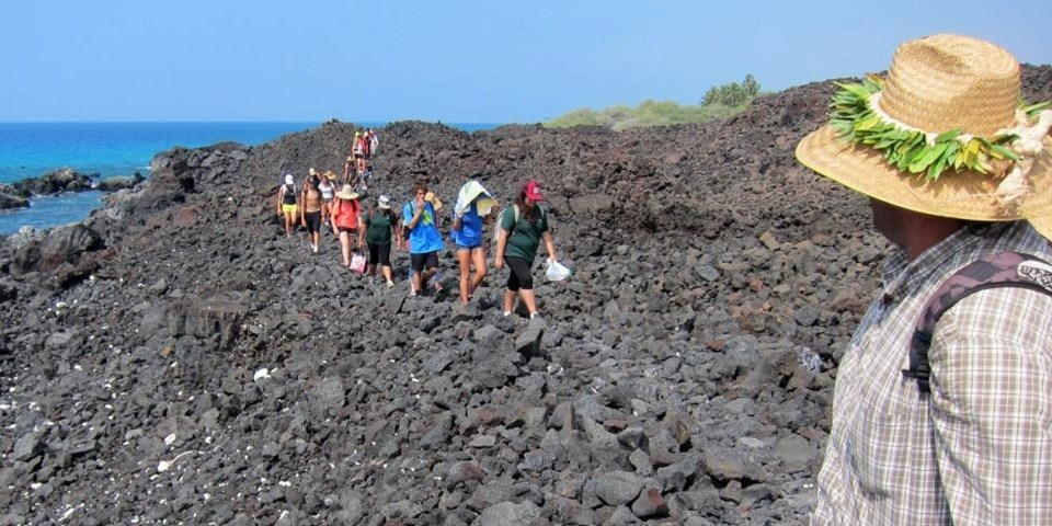 Group of people hike through lava rocks near the ocean