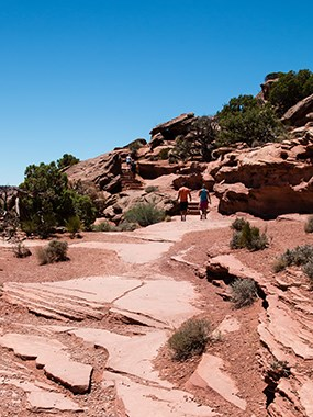 hikers in the distance hiking up red rocks