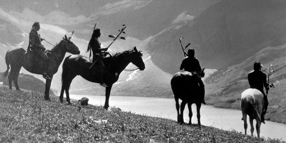 Historic black and white photo of four Native Americans sitting on horses with a mountain and mountain lake in the distance.