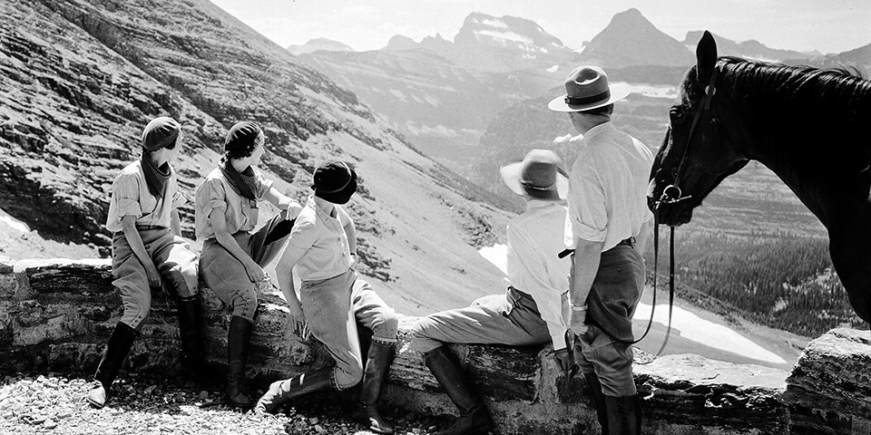 historic black and white photo of three women wearing period clothing sitting on a rock wall next to a standing park ranger and horse looking at distant mountains.