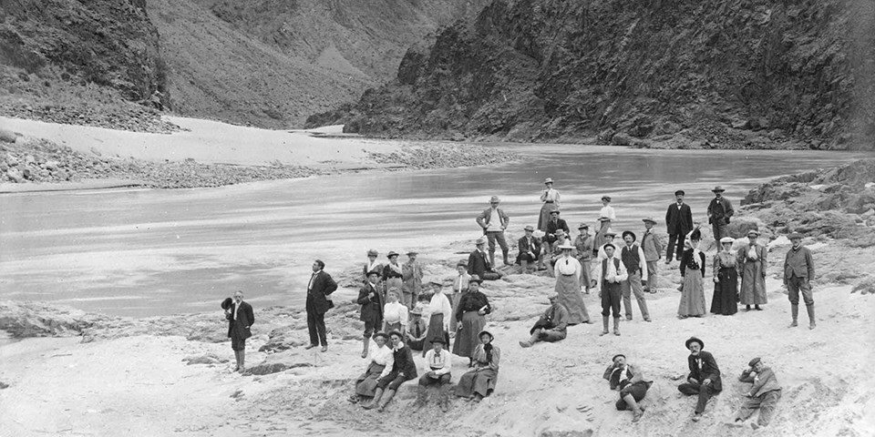 historic black and white photo of people standing next to the Colorado River at Grand Canyon National Park