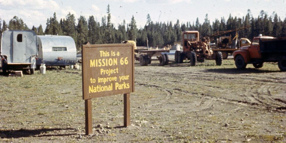 Sign for the Mission 66 project with vintage camping trailers and construction equipment behind it.