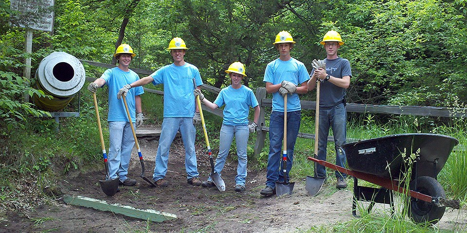 Five youth wearing blue t-shirts and yellow hard hats hold yellow-handled shovels next to a black wheelbarrow.