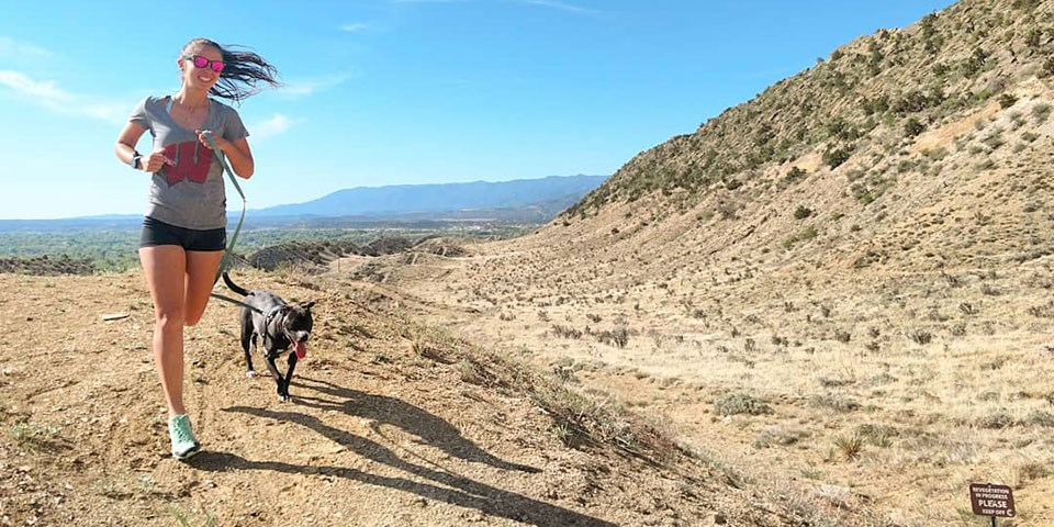 A woman and leashed dog run on a dirt trail
