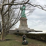 in front of statue of liberty and bare trees, man pushes soil aerator