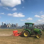 a green tractor drags a mower in front of city