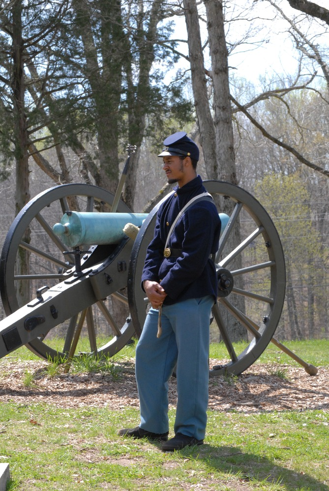 A reenactor of the 12th U.S. Colored Heavy Artillery in uniform standing in front of a canon.