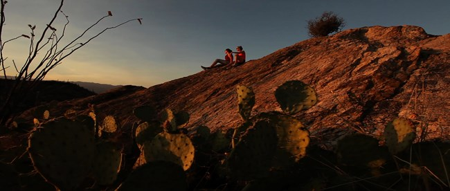 Visitors sit atop a boulder and look at desert landscape.