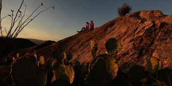 Friends enjoy the Saguaro Wilderness from atop a rock.