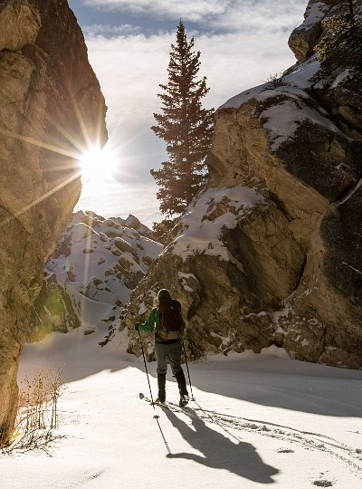 Woman skiing between snowy boulders on sunny day