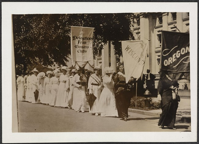 "Photograph of contingents of suffragists marching with banners on street. Banners read: ""Delegations From Womans Clubs"", ""Wisconsin,"" and ""Oregon."""