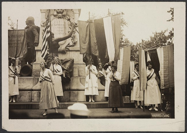 Photograph of five National Woman's Party members demonstrating, with banners, in front of the Lafayette Statue north of the White House in Washington.