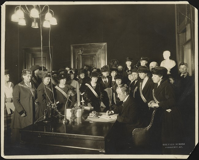 black and white photo of a man at a desk signing a document surrounded by women wearing sashes