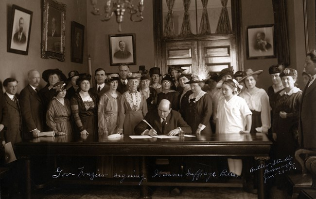 a black and white image of a man at a large desk signing a document surrounded by a group of women