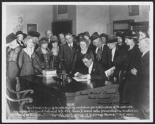 black and white photo of a man at a desk signing a document surrounded by women