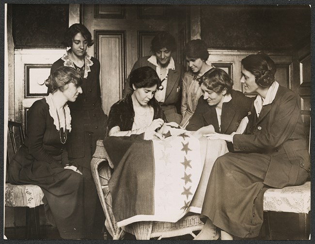 historic black and white image of women sewing a star on a banner