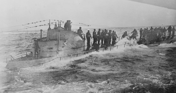 A German submarine crew stands on the deck as waves crash over the sides.
